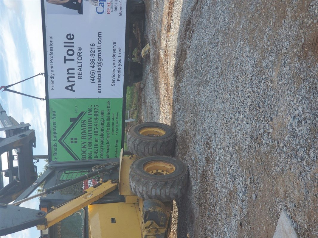 : Utilizing skid steer to hang the sign