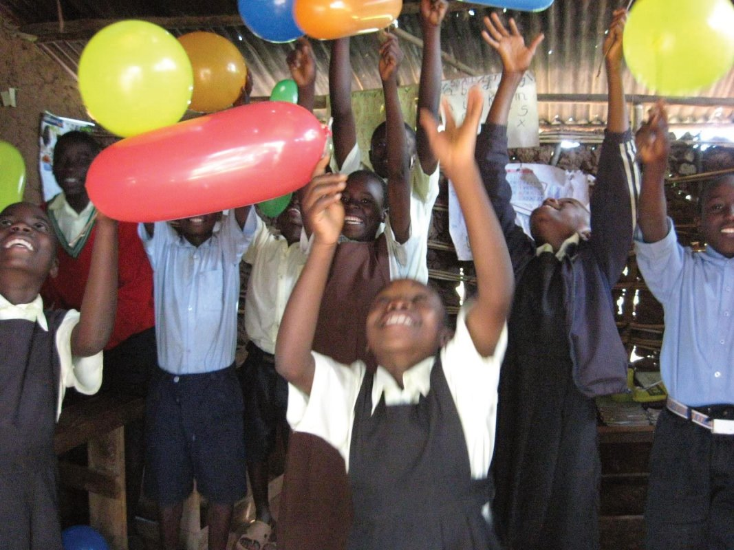 Orphan children celebrating healthy new internal resource qualities using balloons.