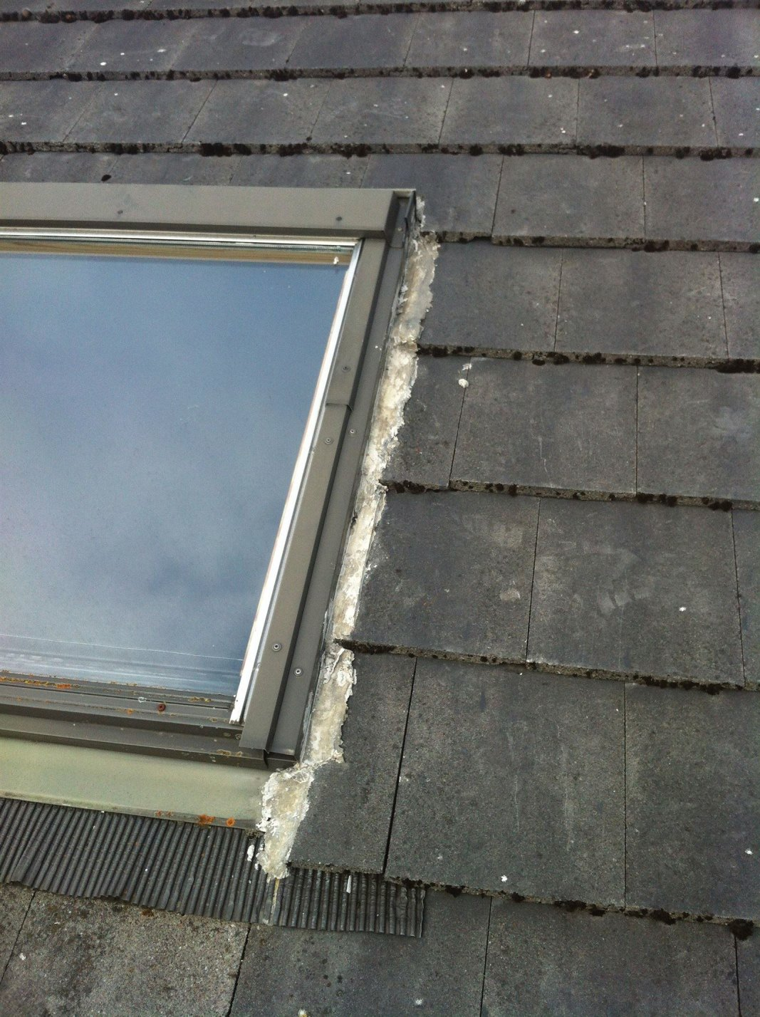 Velux windows come with a flashing that is designed to keep rain and snow out safely. Blocking these with mortar will only lead to further problems.
