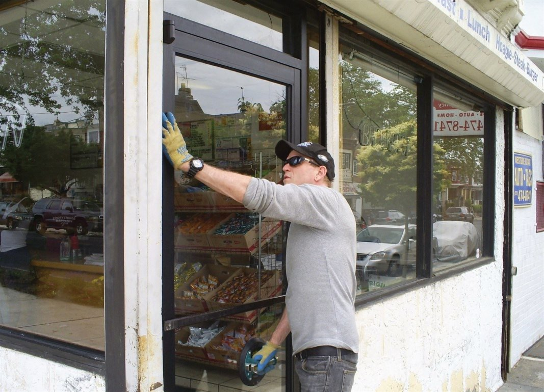 : Making the final adjustments on the new commercial door glass