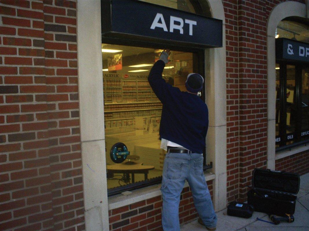 Installing the new bronze plate glass window - Atlas Glass Repair Co