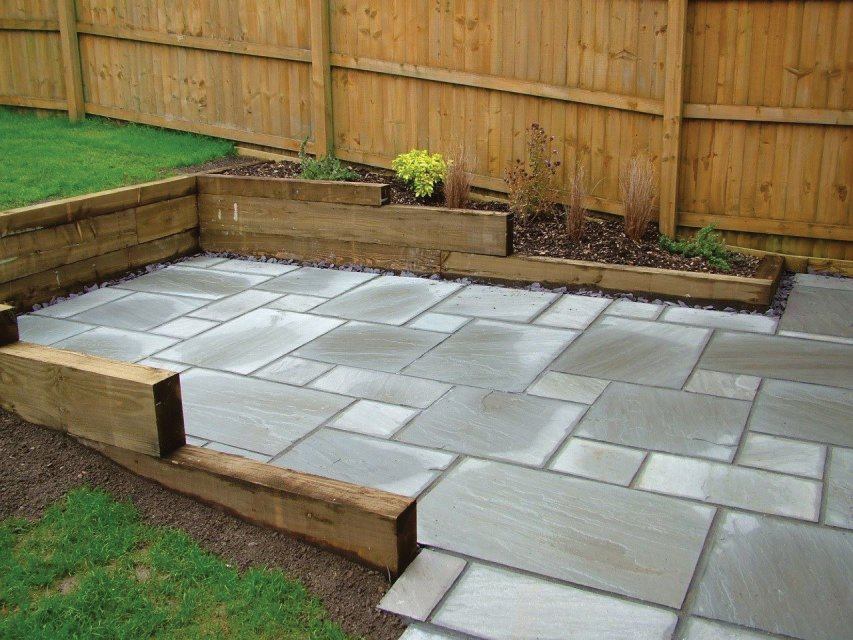 Grey sandstone paving and larch sleeper retaining walls
